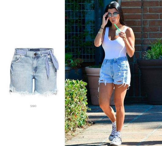 Modelo usa bermuda jeans com blusa branca e tenis branco.