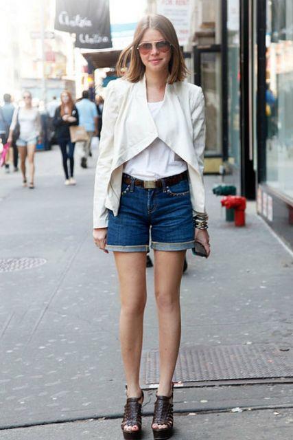 Modelo usa bermuda jeans, com sandalia preta e blazer branco.