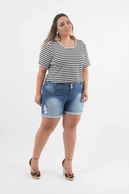Modelo usa blusa listrada de preto e branco com bermuda jeans e sandalia.