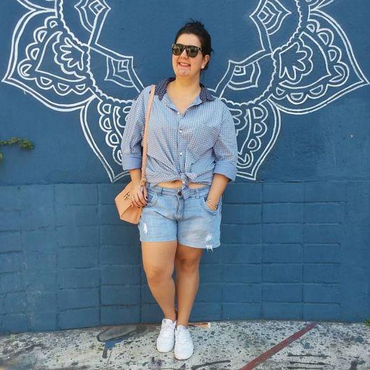 Modelo veste bermuda jeans feminina, tenis branco com camisa azul e bolsa.