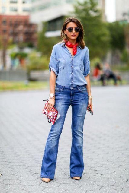 Modelo usa calça flare jeans com camisa, salto e lenço vermelho.