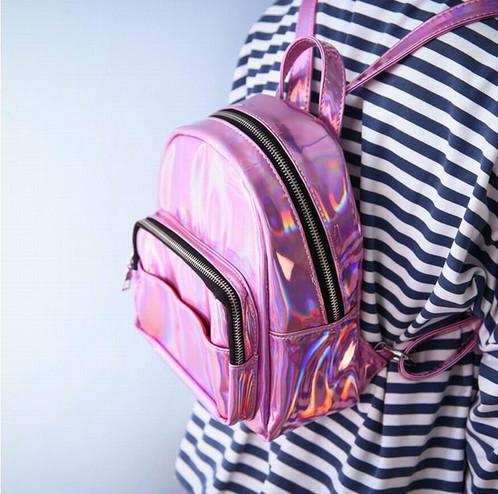 Modelo usa mochila rosa com fecho preto de camiseta listrada em preto e branco.