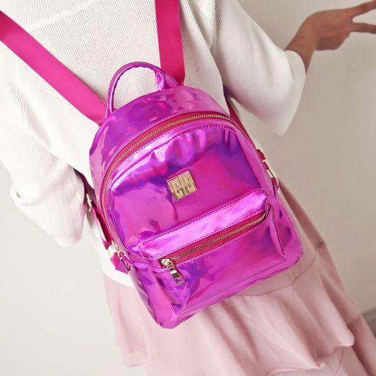 Mochila cor de rosa com bolsinho e alças de tecido.