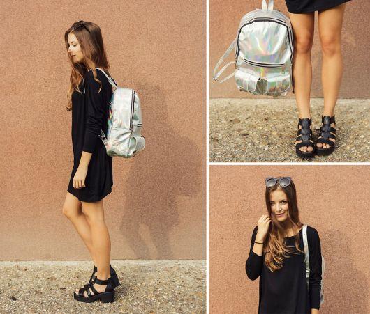 Modelo usa vestido preto e sandália na mesma cor com mochila prata holográfica.