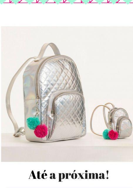 Ilustração com mochila holográfica prata com chaveiros nas cores verde e rosa.