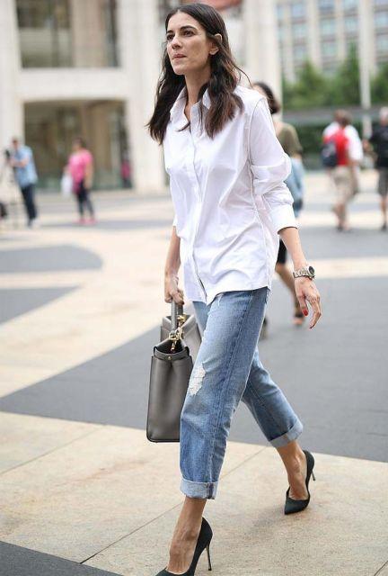 Modelo usa camisa branca oversized e calça jeans e scarpin preto de salto alto.