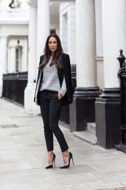 Modelo usa calça preta, blusa manga longa cinza, scarpin preto e blazer na mesma cor.