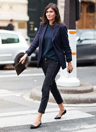 Modelo veste calça jeans preta, blazer azul, blusa azul, clutch e scarpin baixo.