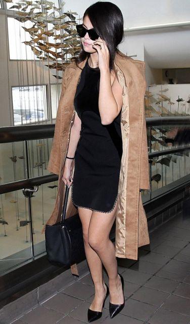 Modelo usa vestido curto preto, casaco e scarpin.