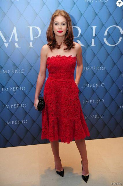 Modelo usa vestido tomara que caia vermelho com scarpin preto.