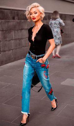 Modelo usa calça jeans azul com bordados, camiseta e scarpin preto.