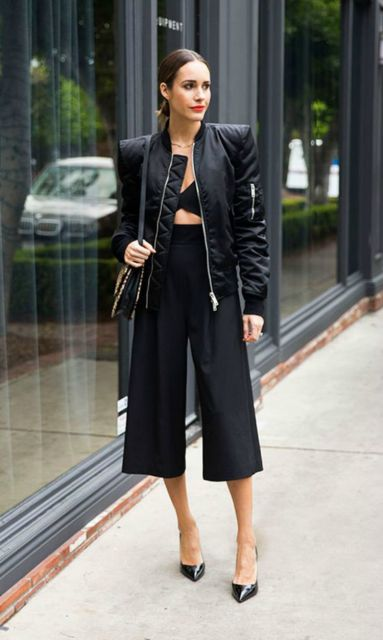 Modelo usa calça preta pantacourt, bustier preto, jaqueta e scarpin.