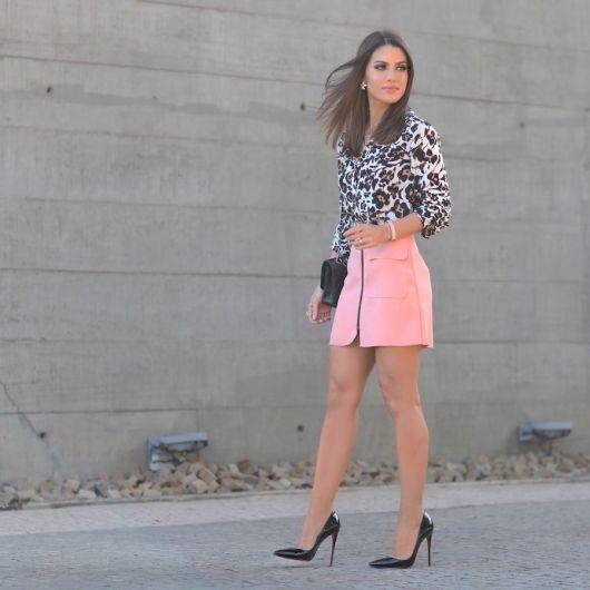 Modelo usa saia rosa, blusa estampada, scarpin preto e clutch.