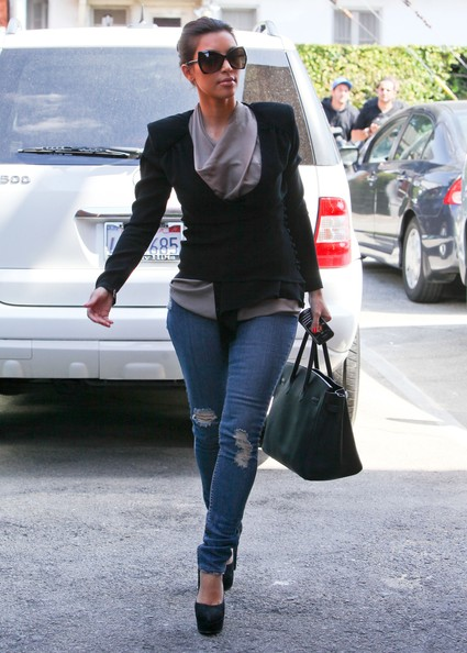 Modelo usa calça jeans, blusa cinza, blazer preto, bolsa e scarpin preto meia pata na mesma cor.