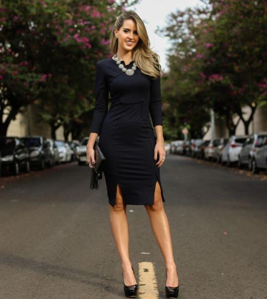 Modelo usa vestido preto midi com scarpin preto meia pata.
