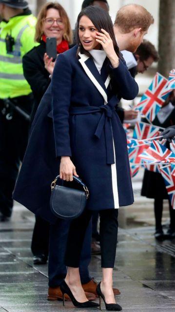 Modelo usa calça preta, casaco azul marinho e scarpin de veludo preto.