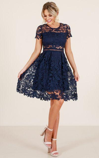 Modelo usa vestido de renda azul marinho com sandalia.