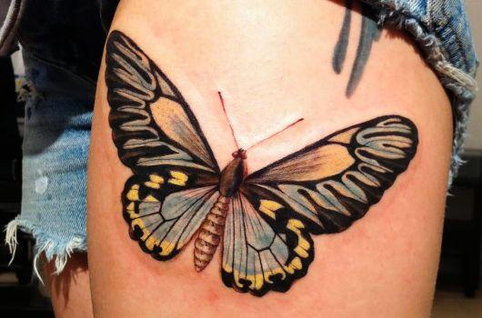Borboleta tatuada nas cores, preto, azul e amarelo.
