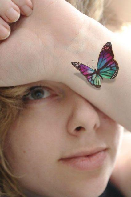 Modelo com tatuagem de borboleta no punho.