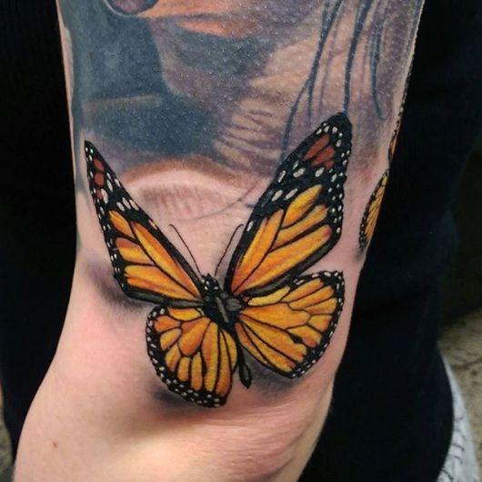 Modelo com tatuagem 3D amarelo com preto.