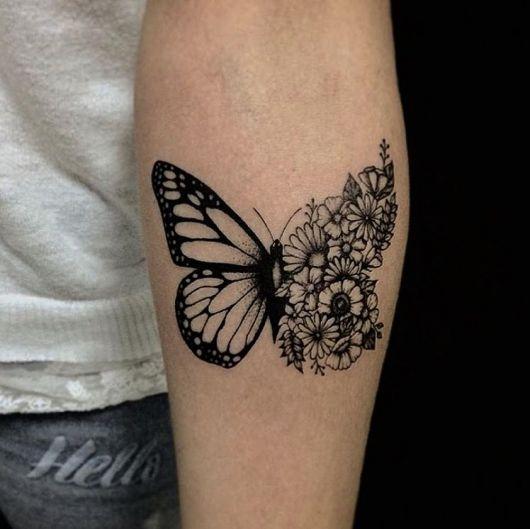 Tatuagem de borboleta preta com flores.