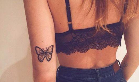 Tatuagem de borboleta atrás do musculo do braço.