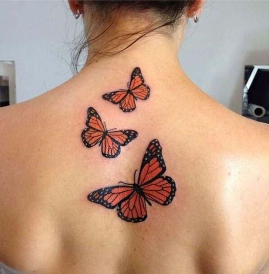Modelo com 3 tatuagens de borboleta nas costas.