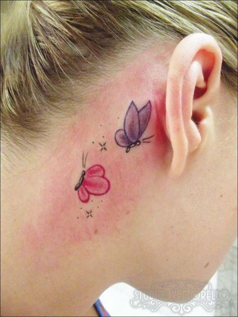 Tatuagem de borboleta rosa e roxa atras da orelha.