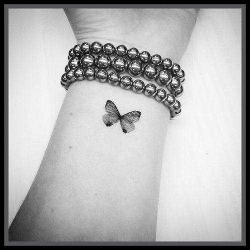 Tatuagem pequena de borboleta preta no pulso.