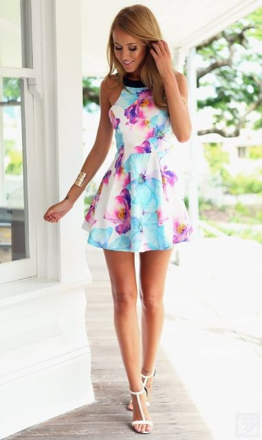 Modelo usa vestido azul curto estampado com rasteira.