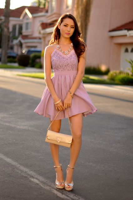 Modelo usa vestido rose, bolsa nude e sandalia de salto prata.