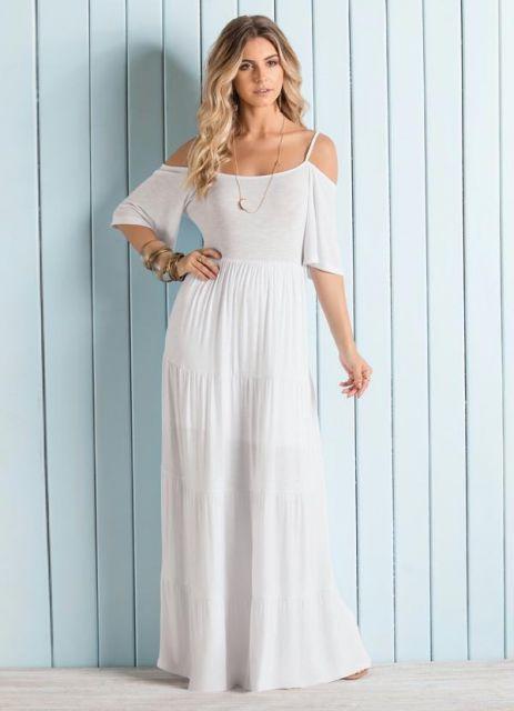 Modelo usa vestido branco longo, rodado com ombro de fora.