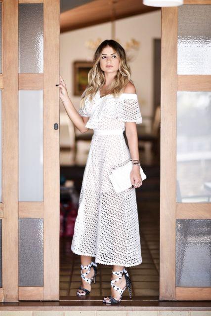 Modelo usa vestido branco, clutch branca e sandalia branca.
