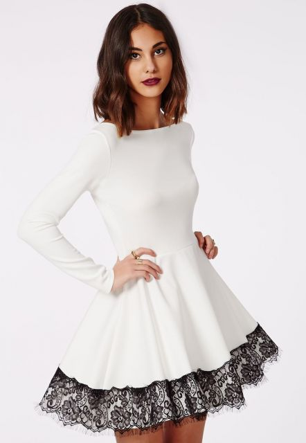 Modelo usa vestido rodado branco manga longa com renda preta.