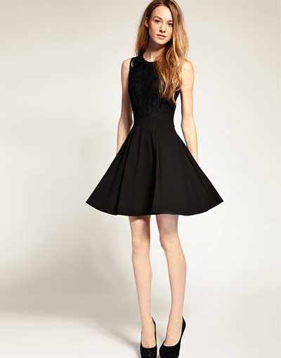 Modelo usa vestido preto rodado e sapato na mesma cor.