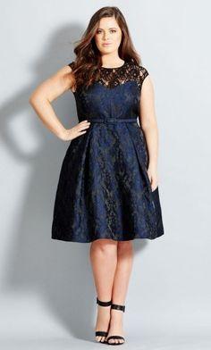 Modelo veste vestido azul marinho com sandali preta.