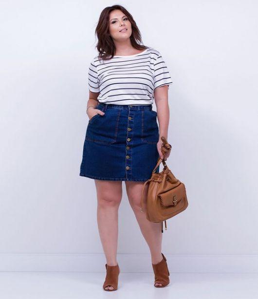 Modelo usa saia de botão azul escuro, blusa branca e preta listrada e bota caramelo.