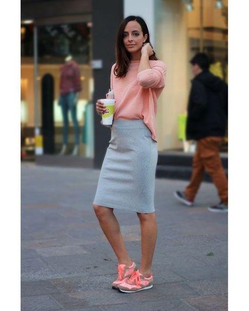 modelo usa saia cinza, blusa e tenis rosa.