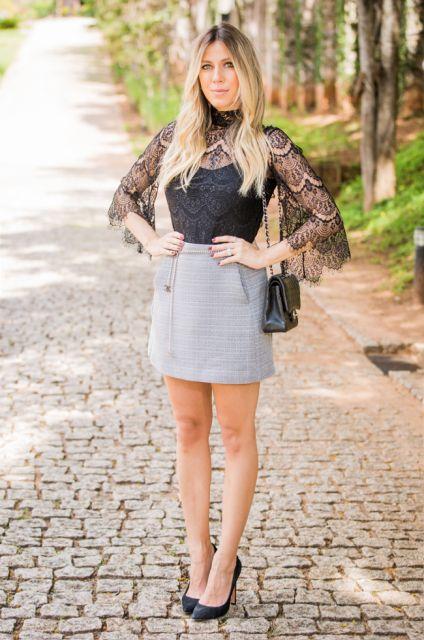 modelo usa saia cinza, scarpin e blusa preta.