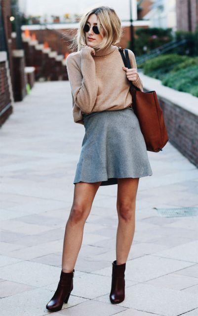 modelo usa saia cinza, bota preta e blusa nude.