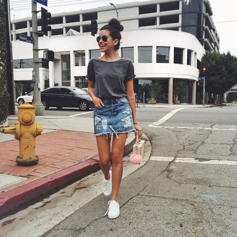 modelo usa saia jeans, camiseta e tenis branco.