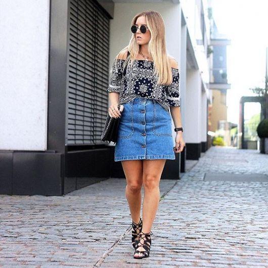 Modelo veste saia jeans azul com sandalia preta gladiadora e blusa preta estampada.