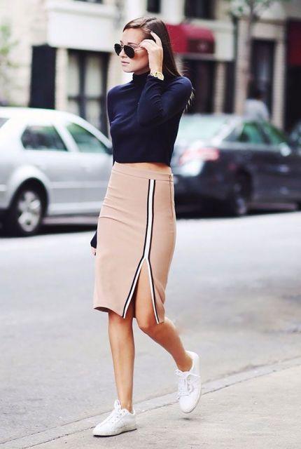 modelo usa saia nude, blusa gola alta azul marinho e tenis branco.