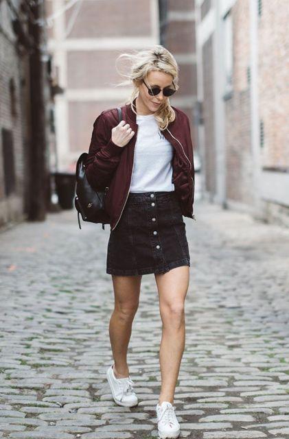modelo usa saia preta de botao, camiseta, tenis e jaqueta jeans vermelha.