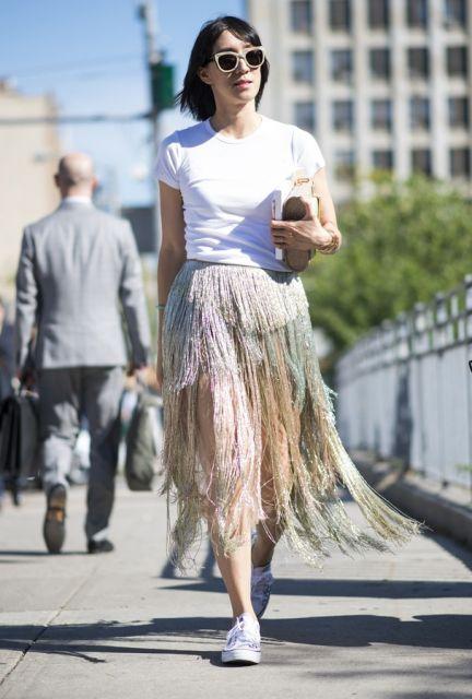 modelo usa saia de franjas, tenis e camiseta branca.