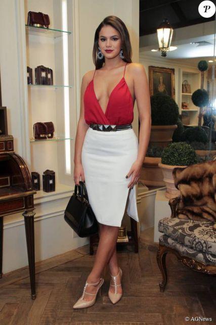 modelo usa saia branca, blusa vermelha e scarpin nude.