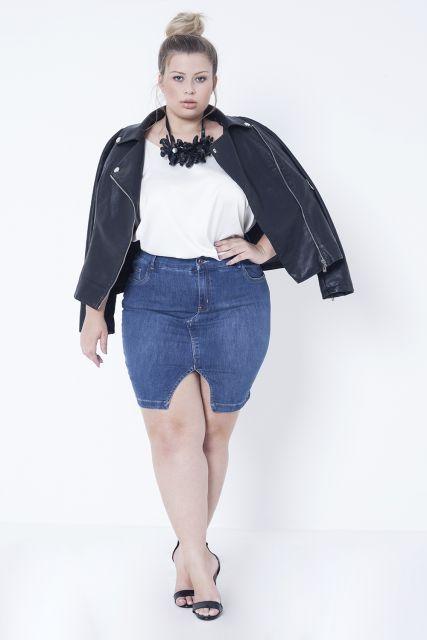 Modelo plus size usa saia jeans, blusa branca, saia jeans, sandalia e jaqueta branca.