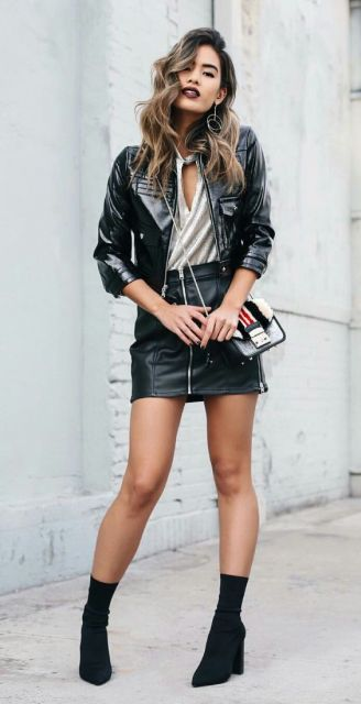 Modelo veste saia preta de couro, jaqueta preta, blusa cinza e bota.