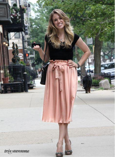 modelo usa saia nude, blusa preta e scarpin.