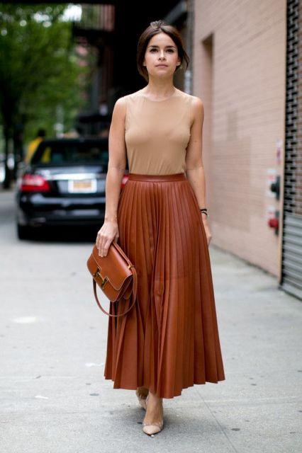 modelo usa saia plissada caramelo, blusa nude e sapato da mesma cor.
